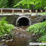 a well designed culvert allowing a stream to pass under a road